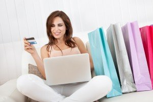 Young Woman Sitting On Sofa Shopping Online With Shopping Bags.